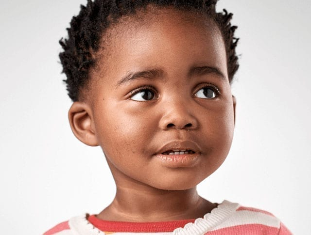 Young African American girl smiles at a Kids' Minds Matter advocate