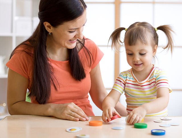 Mother advocate and daughter in pigtails play with Kids' Minds Matter resources