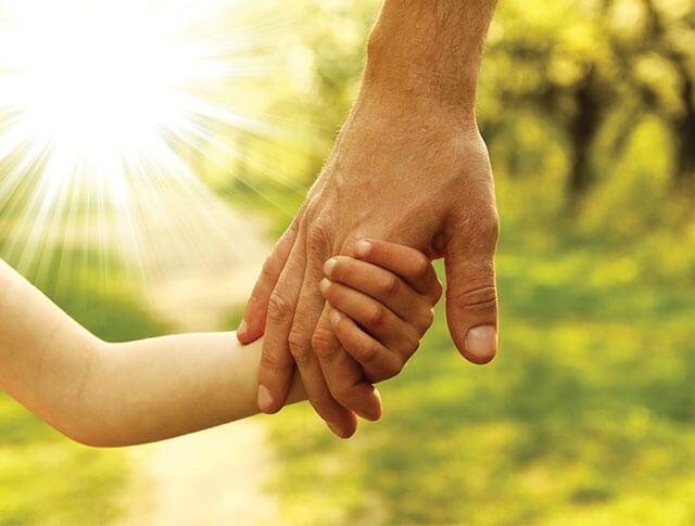 A father holds his child's hand on the way to a Kids' Mind Matter event