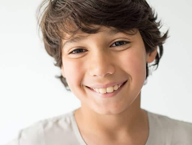 Smiling young boy looks into the camera